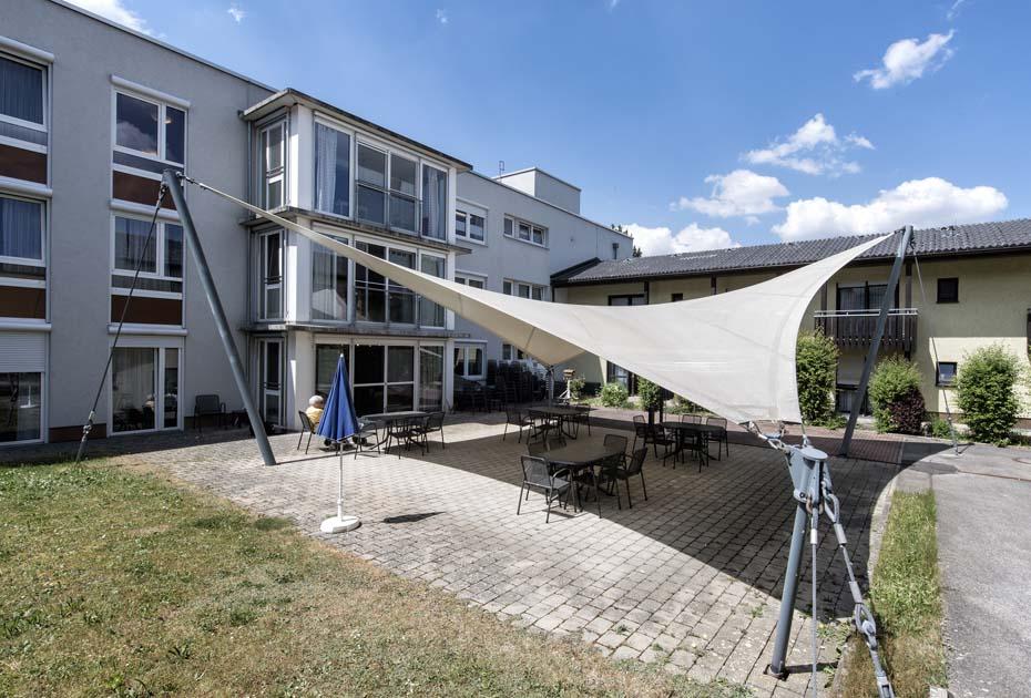 Dieses Bild zeigt den Eingangsbereich des AWO Sozialzentrums Weißenburg mit Sitzplätzen und einem Sonnensegel im Außenbereich